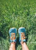 I piedi della donna in scarpe da corsa blu luminose sono in alta erba verde Fotografia Stock Libera da Diritti