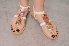 I piedi della donna sono sui sandali. Fotografie Stock