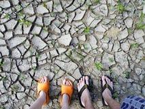I piedi della gente sul suolo incrinato a terra Immagini Stock Libere da Diritti