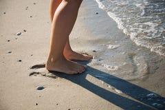 I piedi della ragazza che cammina nel mare ondeggia Fotografie Stock