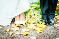 I piedi della sposa e dello sposo in autunno parcheggiano fotografie stock