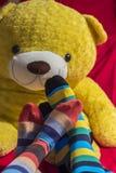 I piedi delle coppie del biglietto di S. Valentino con un orsacchiotto riguardano il fondo Fotografie Stock Libere da Diritti