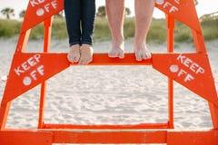 I piedi delle coppie sul supporto del bagnino lasciano stare Fotografia Stock