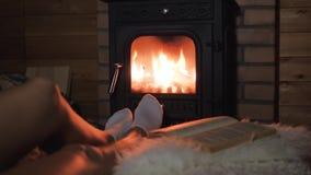 I piedi delle donne si trovano confortevolmente e riscaldano dal fuoco caldo del camino archivi video