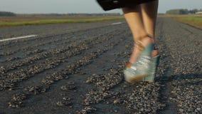 I piedi delle donne sono sulla strada che fa auto-stop l'automobile stock footage