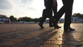 I piedi di tre uomini d'affari che camminano nella città con il chiarore del sole al fondo Gli uomini di affari permutano per lav archivi video