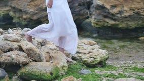 I piedi di una giovane donna come sta camminando su alcune rocce sulla spiaggia video d archivio