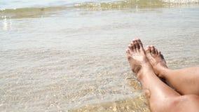 I piedi femminili contro il mare sull'estate tirano, cronometrano per viaggiare Posto vuoto per un testo video 4K stock footage