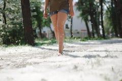 I piedi femminili su erba coperta di pioppo fluff Fotografia Stock Libera da Diritti