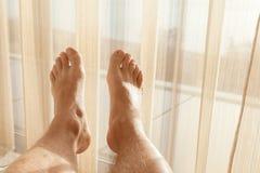 I piedi maschii rilassati pongono vicino all'ampia finestra Immagini Stock Libere da Diritti