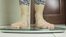 I piedi nudi della donna che stanno sulle scale ed hanno pesato nel bagno - concetto di perdita di peso e di dieta archivi video