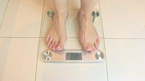I piedi nudi della donna che stanno sulle scale ed hanno pesato nel bagno - concetto di perdita di peso e di dieta video d archivio