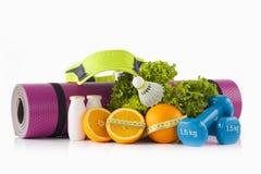 I pilates e la stuoia rosa di yoga si inverdiscono la lattuga, un paio delle teste di legno ricoperte vinile blu ed il volano di  Fotografia Stock Libera da Diritti
