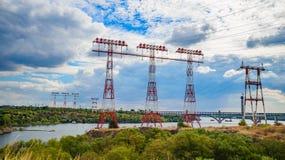 I piloni elettrici attraversano il fiume immagine stock