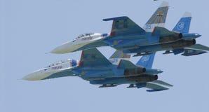 I piloti di due ærei militari SU27 eseguono insieme un giro fotografia stock libera da diritti