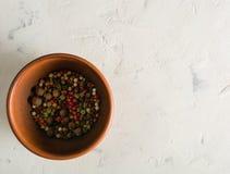 I piselli multicolori dei peperoni in un'argilla lanciano su un fondo di pietra fotografie stock libere da diritti