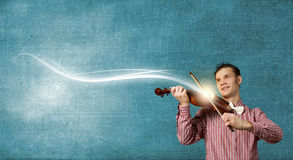 I play violin. Young handsome man in casual playing violin Royalty Free Stock Photography