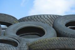 I pneumatici dell'automobile dentro riciclano il mucchio contro cielo blu Immagine Stock