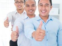 I pollici aumentano gli uomini d'affari asiatici sudorientali Immagini Stock Libere da Diritti