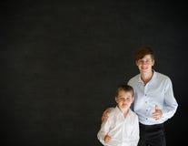 I pollici aumentano l'uomo ed il ragazzo di affari sul fondo della lavagna Fotografia Stock