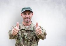 i pollici del soldato aumentano e sorridere Muro di cemento fotografia stock libera da diritti