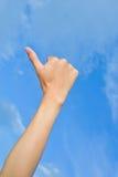 I pollici della mano del primo piano aumentano il fondo del cielo blu del segno Immagine Stock