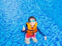 I pollici felici del ragazzino su con il giubbotto di salvataggio arancio si diverte e godono di nella piscina fotografie stock