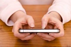 I pollici femminili stanno digitando su un telefono astuto Fotografia Stock Libera da Diritti