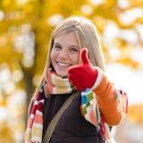 I pollici sorridenti della ragazza dell'adolescente di autunno aumentano la foresta Immagini Stock