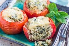 I pomodori al forno farciti con la quinoa e gli spinaci hanno completato con formaggio fuso sul piatto, orizzontale Fotografie Stock