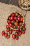 I pomodori ciliegia, è piccoli pomodori sulla cima e sul tessuto di canestro di legno immagine stock libera da diritti