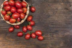 I pomodori ciliegia, è piccoli pomodori sulla cima e sul tessuto di canestro di legno fotografia stock libera da diritti