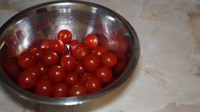 I pomodori ciliegia cadono in una ciotola del metallo al rallentatore archivi video