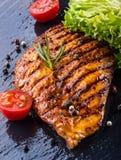 I pomodori ciliegia dell'olio d'oliva del petto di pollo della bistecca pepano e le erbe dei rosmarini Fotografie Stock