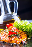 I pomodori ciliegia dell'olio d'oliva del petto di pollo della bistecca pepano e le erbe dei rosmarini Fotografie Stock Libere da Diritti
