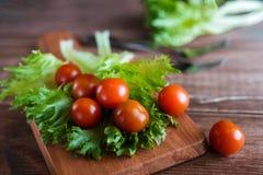I pomodori ciliegia e l'insalata va sul tagliere con il fuoco molle sui precedenti Vista superiore Copi lo spazio del testo Immagini Stock Libere da Diritti