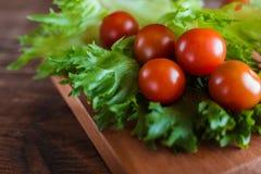 I pomodori ciliegia e l'insalata va sul tagliere con il fuoco molle sui precedenti Vista superiore Copi lo spazio del testo Fotografia Stock