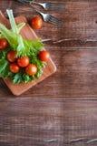 I pomodori ciliegia e l'insalata va sul tagliere con il fuoco molle sui precedenti Vista superiore Copi lo spazio del testo Fotografie Stock