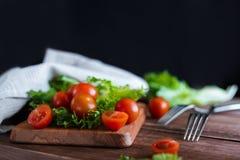 I pomodori ciliegia e l'insalata va sul tagliere con il fuoco molle sui precedenti Vista superiore Copi lo spazio del testo Immagini Stock