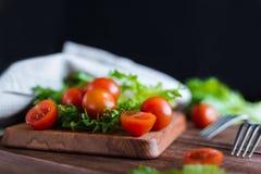 I pomodori ciliegia e l'insalata va sul tagliere con il fuoco molle sui precedenti Vista superiore Copi lo spazio del testo Fotografia Stock Libera da Diritti