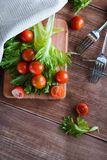 I pomodori ciliegia e l'insalata va sul tagliere con il fuoco molle sui precedenti Vista superiore Copi lo spazio del testo Fotografie Stock Libere da Diritti