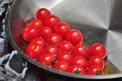 I pomodori ciliegia sono arrostiti in olio d'oliva sopra carbone Immagine Stock