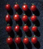 I pomodori ciliegia su fondo nero hanno sistemato in un modo lineare Fotografia Stock