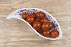 I pomodori dello sherry in una porcellana lanciano su fondo di legno Immagine Stock