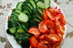 I pomodori ed i cetrioli affettati si trovano su un piatto fotografie stock libere da diritti