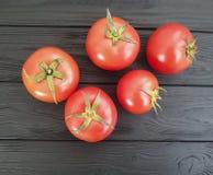 I pomodori freschi su un vegetariano antiossidante di legno nero dell'ingrediente raccolgono immagine stock