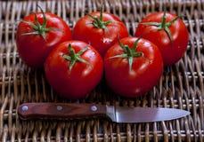 I pomodori maturi e un coltello sul vimine sorgono Fotografie Stock