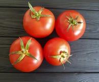 I pomodori naturali freschi su un vegetariano antiossidante di legno nero dell'ingrediente raccolgono immagini stock libere da diritti