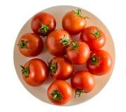 I pomodori rossi su un piatto hanno isolato la vista superiore del fondo Immagine Stock