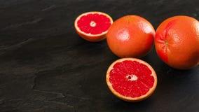 I pompelmi rosa-rosso, un agrume sono dimezzato, sull'ardesia nera come il bordo, ampia foto con spazio vuoto per la parte di sin immagine stock libera da diritti